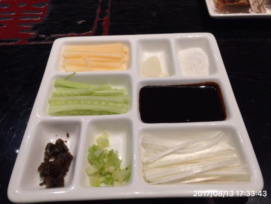 円形の餅に、みそを塗って、いろいろな薬味と北京ダックを乗せて折り曲げて食べます。